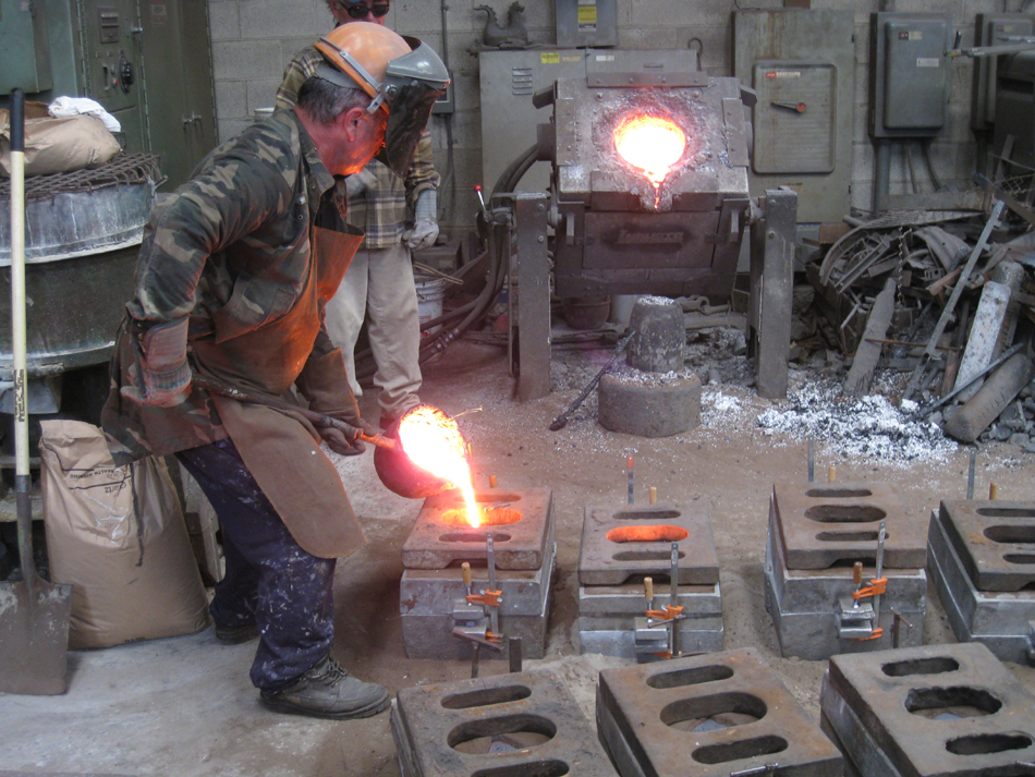 Fence -- Swiss Foundry -- pouring metal into molds for fence elements.