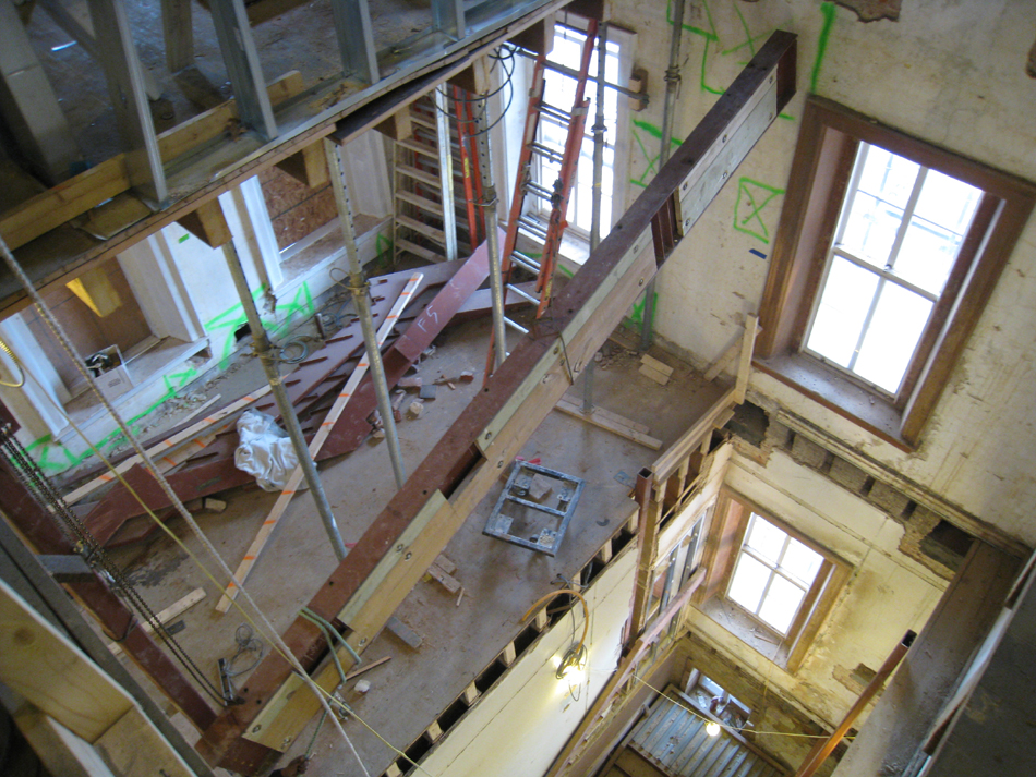 Third Floor--Looking down east stairwell as beam is being raised into place