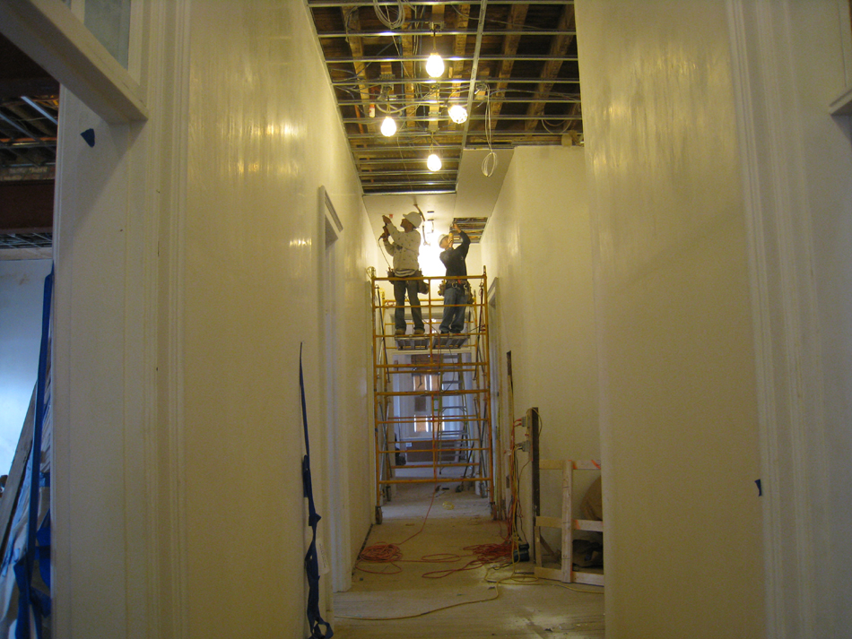 Second Floor--Installing drywall on the ceiling in the central corridor (looking west) - March 14, 2011